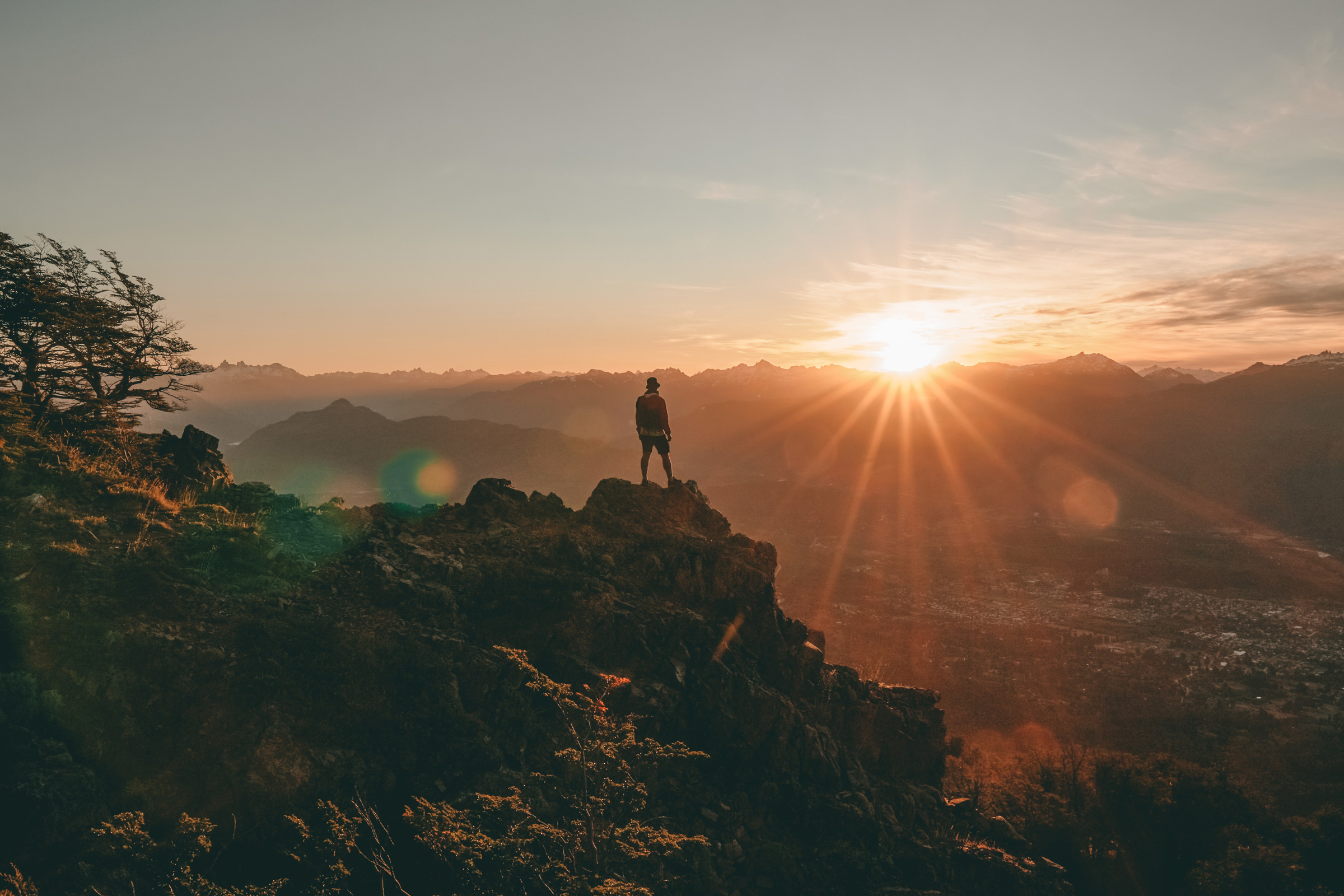 Man Standing on top of a Mountain looking towards the Sun.